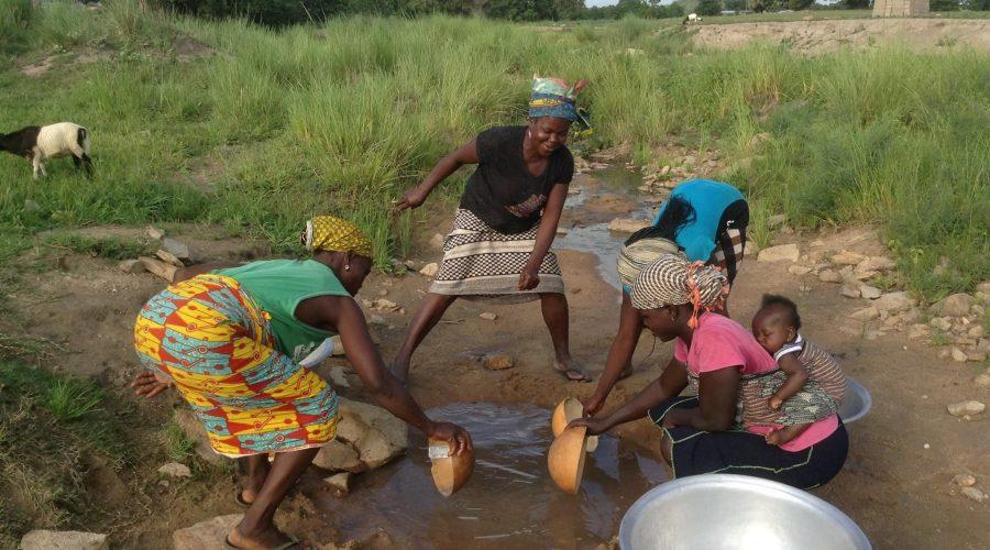 Naiset keräävät vettä ojasta.